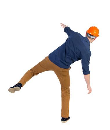 hombre cayendo: Equilibrio joven. o esquivar el hombre que cae. trabajador de la construcción del casco cae. Vista posterior recogida de las personas. trasero vista de la persona. Aislado sobre fondo blanco. un hombre con una camisa azul y un casco en equilibrio sobre la pierna derecha.