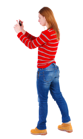 compact camera: back view of standing young beautiful  woman  using a mobile phone. girl  watching. Rear view people collection.  backside view of person.  Isolated over white background. The blonde in a red striped sweater photographing something left compact camera.