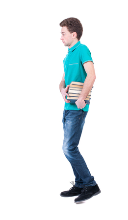 treading: side view of going  man carries a stack of books. walking young guy . Rear view people collection.  backside view of person.  Isolated over white background. Curly man in a turquoise jacket goes to the side with a bundle of books.