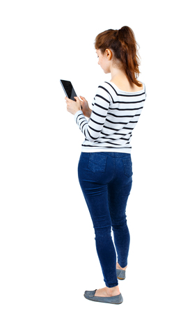 back view of standing young beautiful  woman using a mobile phone or tablet computer. girl  watching. Rear view people collection.  backside view of person.  Isolated over white background. Girl in a striped sweater standing sideways and running on the ta Stock Photo