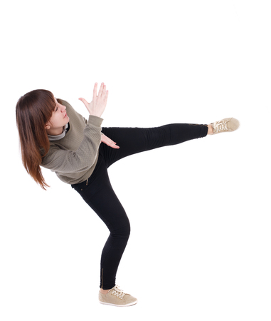 wimp: back view of woman funny fights waving his arms and legs. Rear view people collection. backside view of person.  Isolated over white background. A girl in a gray sweater has foot.
