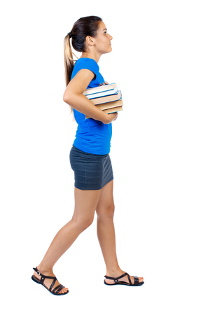 Girl comes with  stack of books. side view. Rear view people collection.  backside view of person.  Isolated over white background. girl in a short skirt and a blue T-shirt goes to the side with books and looking up.