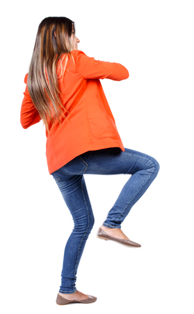 back view of woman funny fights waving his arms and legs. Rear view people collection. backside view of person.  Isolated over white background. business woman in a red jacket kicks. Stock Photo