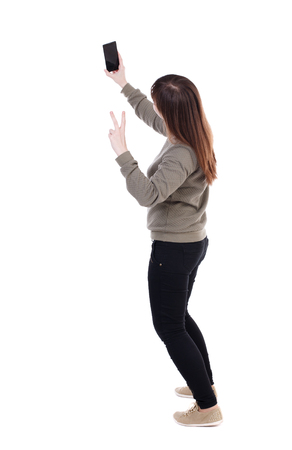 black and white photograph: back view of standing young beautiful  woman  using a mobile phone. girl  watching. Rear view people collection.  backside view of person.  Isolated over white background. Girl showing victory sign making selfie.