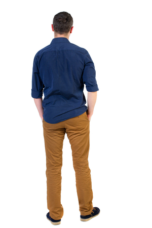 his shirt sleeves: Back view of man . Standing young guy. Rear view people collection.  backside view of person.  Isolated over white background.a man in a blue shirt with the sleeves rolled up, standing with his hands in his pocket. Stock Photo