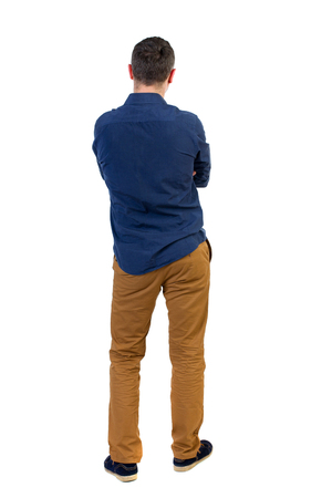 his shirt sleeves: Back view of man . Standing young guy. Rear view people collection.  backside view of person.  Isolated over white background.a man in a blue shirt with the sleeves rolled up, standing with her hands folded on his chest. Stock Photo