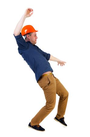 hombre cayendo: Equilibrio joven. o esquivar el hombre que cae. trabajador de la construcción del casco cae. Vista posterior recogida de las personas. trasero vista de la persona. Aislado sobre fondo blanco. Ingeniero en casco protector cae deslizándose Foto de archivo