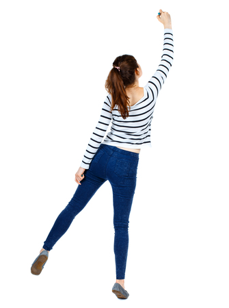 back view of writing beautiful woman. Rear view people collection.  backside view of person. Isolated over white background. Girl in a striped sweater standing on tiptoes and draws marker. Stock Photo