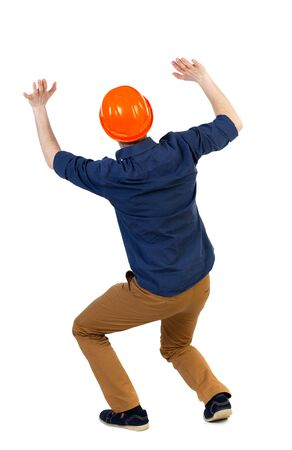 rolled up sleeves: back view business man protective construction helmet protects hands from what is falling from above. Rear view people collection.  backside view of person.  Isolated over white background. The engineer in a blue shirt with the sleeves rolled up and a hel Stock Photo