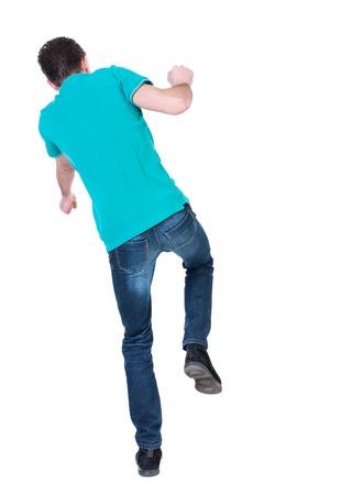 hombre cayendo: Equilibrio joven. o esquivar el hombre que cae. Vista posterior recogida de las personas. trasero vista de la persona. Aislado sobre fondo blanco. Hombre rizado en una chaqueta de color turquesa cae hacia un lado. Foto de archivo