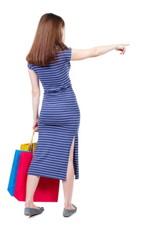 back view of woman  with shopping bags pointing . beautiful brunette girl in motion.  backside view of person.  Rear view people collection. Isolated over white background. The brunette in a blue striped dress standing with shopping bags and showing thumb