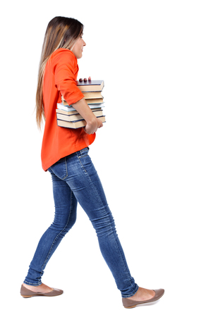 Girl comes with  stack of books. side view. Rear view people collection.  backside view of person.  Isolated over white background. girl in a red jacket with difficulty carries a lot of books under his arm.