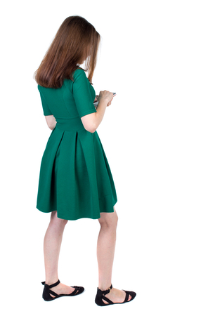 back view of standing young beautiful  woman using a mobile phone or tablet computer. girl  watching. Rear view people collection.  backside view of person.  Isolated over white background. The slender brunette in a green short dress stands sideways looki