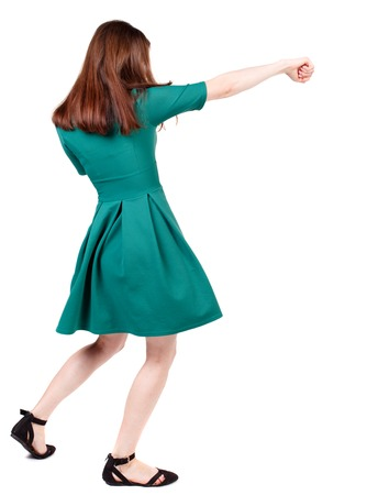 loser: skinny woman funny fights waving his arms and legs. Isolated over white background. The slender brunette in a green short dress causes a sharp blow.