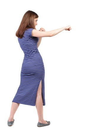 wimp: skinny woman funny fights waving his arms and legs. Isolated over white background. The brunette in a blue striped dress stands sideways and hit his foot.