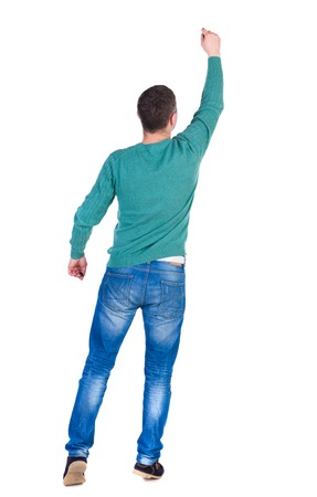 pulled over: back view of writing business man. Rear view people collection.  backside view of person. Isolated over white background. A man in a green jacket and jeans pulled up to write a marker on the wall.