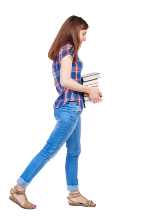 učebnice: Girl comes with  stack of books. side view. Rear view people collection.  backside view of person.  Isolated over white background. Girl in a plaid shirt goes to the sad side with textbooks. Reklamní fotografie