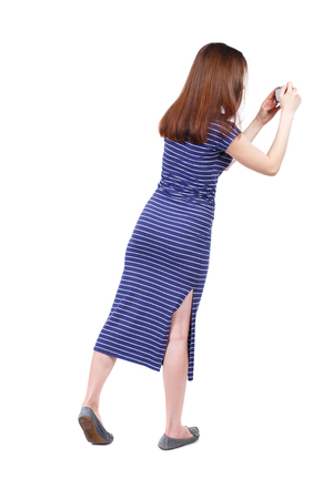 compact camera: back view of standing young beautiful  woman  and using a mobile phone. girl  watching. Rear view people collection.  backside view of person.  Isolated over white background. The brunette in a blue striped dress photographed on a compact camera standing  Stock Photo