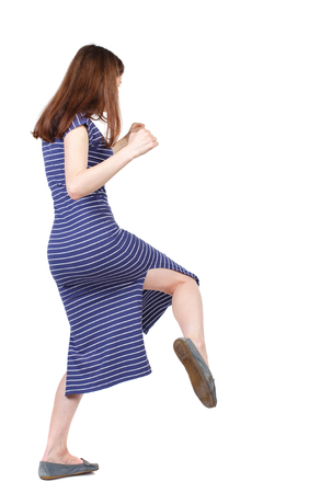 skinny woman funny fights waving his arms and legs. Isolated over white background. The brunette in a blue striped dress fighting and kicking. Stock Photo