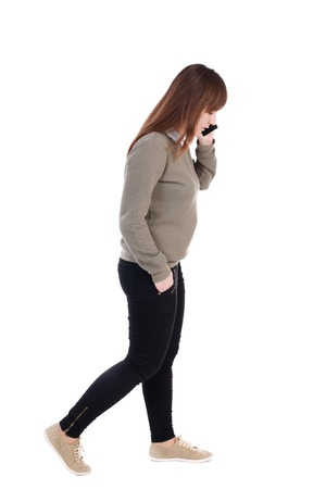 side view of a woman walking with a mobile phone. back view of girl in motion.  backside view of person.  Rear view people collection. Isolated over white background. with his hand in the pocket of a girl talking on the phone and go to the right.