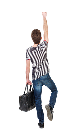 striped vest: Back view of  man with bag.  Raised his fist up in victory sign.  Rear view people collection.  backside view of person.  Isolated over white background. Curly boy in a striped vest with a bag depicts a superhero.