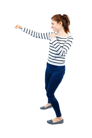 back view of woman funny fights waving his arms and legs. Rear view people collection. backside view of person.  Isolated over white background. Girl in a striped sweater boxing. Stock Photo