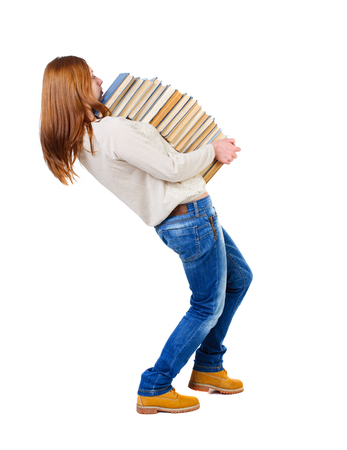 strongly: Girl carries a heavy pile of books. back view.  Rear view people collection.  backside view of person.  Isolated over white background. Blonde in a white blouse strongly leaned back under the weight of a stack of textbooks. Stock Photo