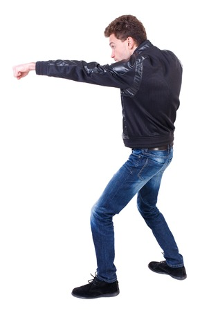 wimp: back view of guy funny fights waving his arms and legs. Isolated over white background. Rear view people collection.  backside view of person. Curly guy in a black leather jacket stretched out his hand with his fist.