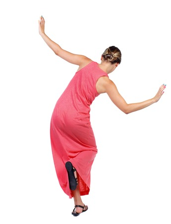 Balancing young woman.  or dodge falling woman. Rear view people collection.  backside view of person.  Isolated over white background. A slender woman in a long red dress is standing on one leg.