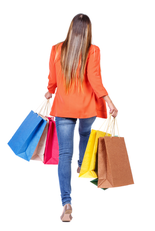 back view of a woman jumping with shopping bags. beautiful brunette girl in motion.  backside view of person.  Rear view people collection. Isolated over white background. girl in a red jacket jumping with paper bags.