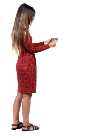 back view of standing young beautiful  woman  and using a mobile phone. girl  watching. Rear view people collection.  backside view of person.  Isolated over white background. The girl in red plaid dress standing sideways and looking at the tablet.