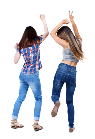 Back view of two dancing young women. Dance party. girls teens dance, enjoy and express positive emotions and having fun. backside view of person.  Rear view people collection. Isolated over white background. Two young girls in jeans dancing