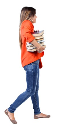 Girl comes with  stack of books. side view. Rear view people collection.  backside view of person.  Isolated over white background. student in a red jacket with difficulty carries a lot of books under his arm.