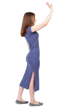 Side view of beautiful woman welcomes. Young teenager girl in jeans hand waving from. Rear view  people collection.  backside view of person.  Isolated over white background. The brunette in a blue striped dress stands sideways and waving his hand in gree Stock Photo