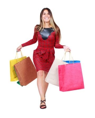 go shopping: front view of a woman jumping with shopping bags. beautiful brunette girl in motion.  front view of person.  Isolated over white background. The girl in red plaid dress runs to meet us smiling and holding colorful shopping bags.