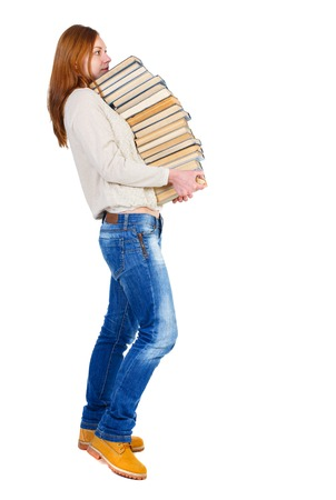 Girl comes with  stack of books. side view. Rear view people collection.  backside view of person.  Isolated over white background. The girl in a white warm sweater tries to hold a heavy stack of books.