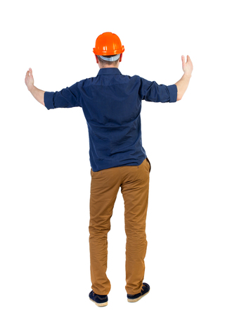 his shirt sleeves: Back view of builder in helmet shows thumbs up.   Rear view people collection.  backside view of person.  Isolated over white background. The engineer in a blue shirt with the sleeves rolled up and a helmet holds out his hands in greeting. Stock Photo