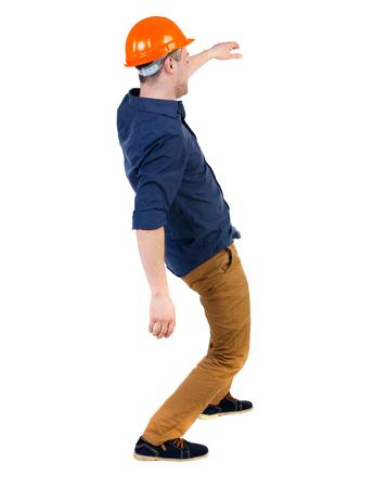 hombre cayendo: Equilibrio joven. o esquivar el hombre que cae. trabajador de la construcción del casco cae. Vista posterior recogida de las personas. trasero vista de la persona. Aislado sobre fondo blanco. un hombre en un casco protector cae