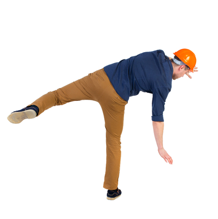 hombre cayendo: Equilibrio joven. o esquivar el hombre que cae. trabajador de la construcción del casco cae. Vista posterior recogida de las personas. trasero vista de la persona. Aislado sobre fondo blanco. un hombre con una camisa azul y un casco caídas tratando de mantener con el pie derecho.