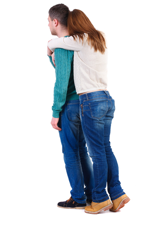 Back view of young embracing couple (man and woman) hug and look into the distance. backside view of person.  Isolated over white background. The girl in warm jacket standing on tiptoes hugging man from behind.