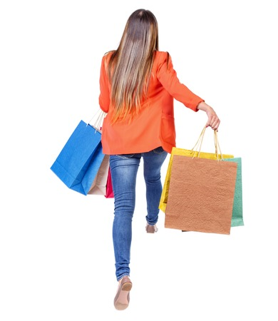 persona saltando: back view of a woman jumping with shopping bags. beautiful brunette girl in motion.  backside view of person.  Rear view people collection. Isolated over white background. girl in a red jacket jumping with colored bags.