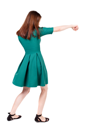 wimp: skinny woman funny fights waving his arms and legs. Isolated over white background. The slender brunette in a green short dress has outstretched arm.
