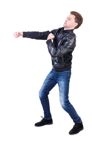 wimp: back view of guy funny fights waving his arms and legs. Isolated over white background. Rear view people collection.  backside view of person.Curly guy in a black leather jacket clumsily fighting. Stock Photo