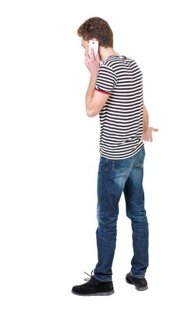 back view of business man talking on mobile phone.    rear view people collection. Isolated over white background. backside view of person. Curly boy in a striped vest emotionally talking on the phone. Stock Photo