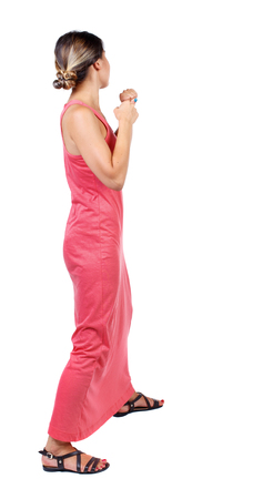 wimp: skinny woman funny fights waving his arms and legs. Isolated over white background. A slender woman in a long red dress is standing with clenched fists.