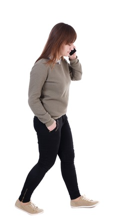 side view of a woman walking with a mobile phone. back view of girl in motion.  backside view of person.  Rear view people collection. Isolated over white background. with his hand in the pocket of a girl talking on the phone