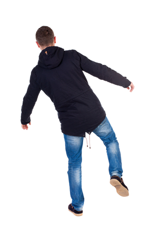hombre cayendo: Balancing young man.  or dodge the falling man. Rear view people collection.  backside view of person.  Isolated over white background. Man in warm jacket falls while standing on the left leg. Foto de archivo