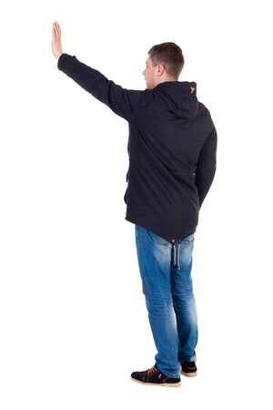 Back view of beautiful man welcomes. man hand waving from. Rear view  people collection.  backside view of person.  Isolated over white background. Man in warm jacket waving his right hand in greeting to the left.