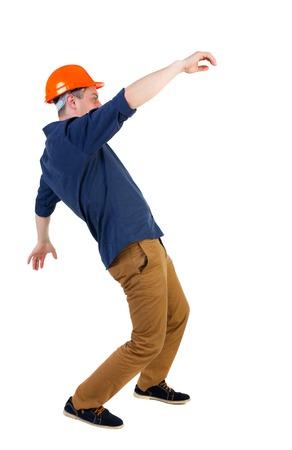 hombre cayendo: Equilibrio joven. o esquivar el hombre que cae. trabajador de la construcción del casco cae. Vista posterior recogida de las personas. trasero vista de la persona. Aislado sobre fondo blanco. Ingeniero en casco protector cae agitando los brazos. Foto de archivo