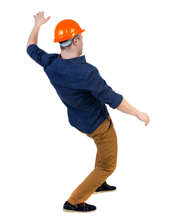 strongly: Balancing young man.  or dodge the falling man. worker in construction helmet falls. Rear view people collection.  backside view of person.  Isolated over white background. a man in a helmet is strongly leaned back balancing. Stock Photo